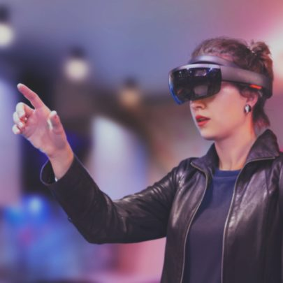 Portrait of young Caucasian woman using augmented and virtual reality with holographic hololens glasses. Pink, magenta and blue background. Future technology concept.